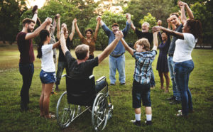 Group of people of all ages uplifting hands in group