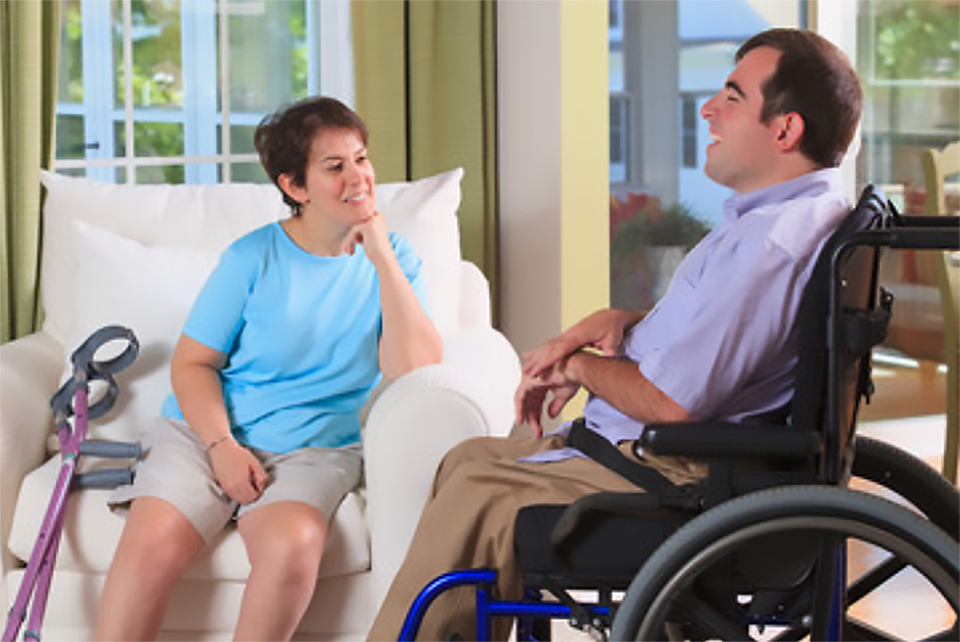 Man and woman couple with cerebral palsy sitting talking together