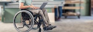 Man in wheelchair typing on laptop