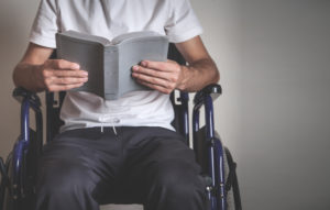Person in wheelchair reading the Bible