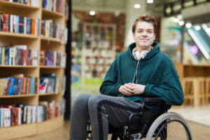 Smiling teenage boy in wheelchair at the library