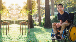 Smiling young Asian boy sitting in a wheelchair in a garden