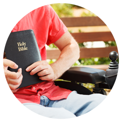 Young man in a wheelchair holding a bible