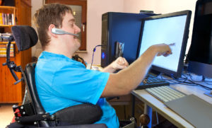 Young man with cerebral palsy in blue shirt in wheelchair working at computer