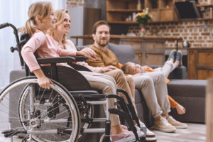 Young smiling girl in wheelchair sitting with family in living room laughing joyfully